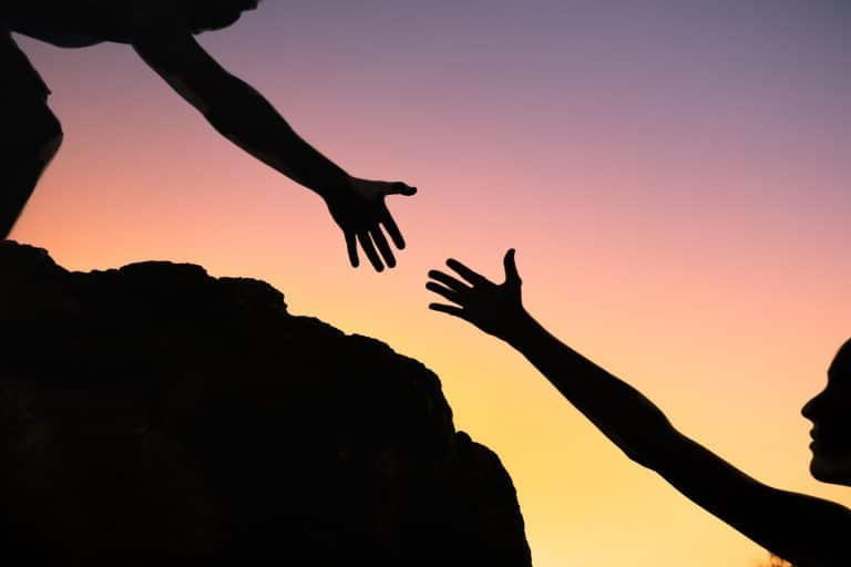 trust in a relationship - photo of hand reaching to help another up a mountain